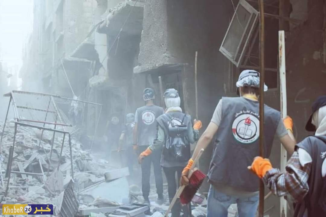متطوعون من اتحاد طلبة فلسيطين يشاركون في ازالة الركام من منازل مخيم اليرموك المدمرة للإسراع في عملية رفع الانقاض