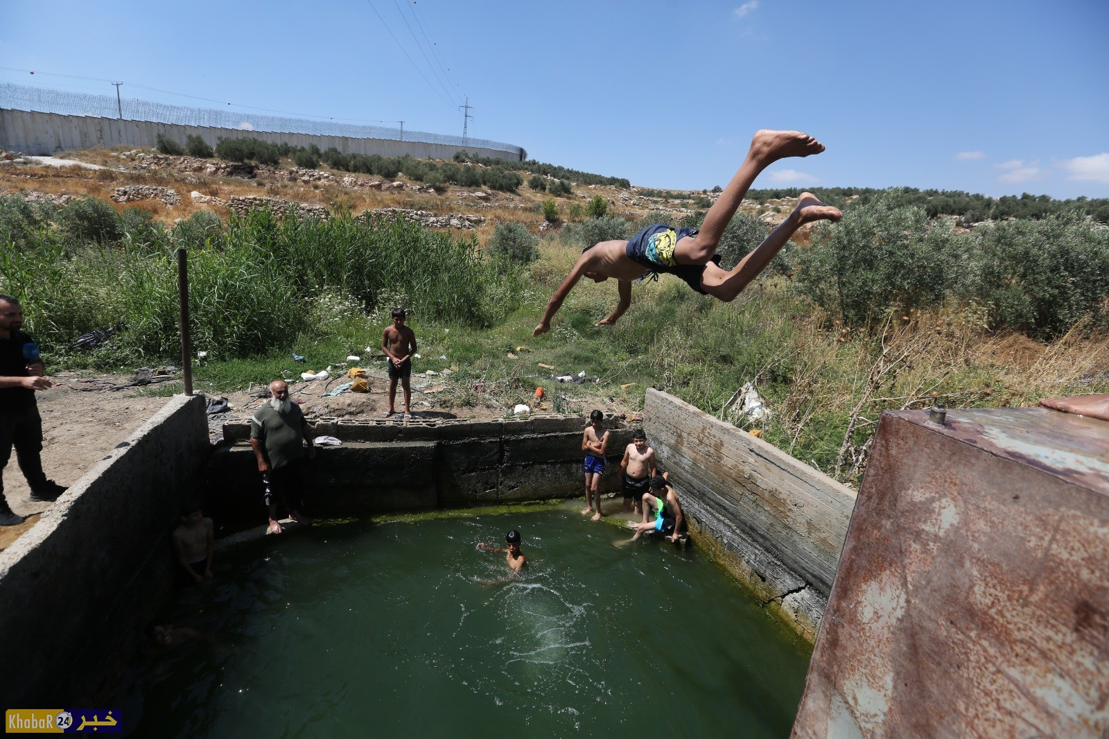 مواطنون يسبحون في عين ماء حاصرها الجدار غرب الخليل