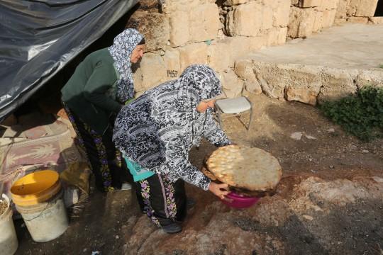 الحاجة جازيه ابو كباش (80عام) والحاجة غزلان ابو كرش (50عاما) من بلدة السموع جنوب الخليل تعدان خبز الطابون.   