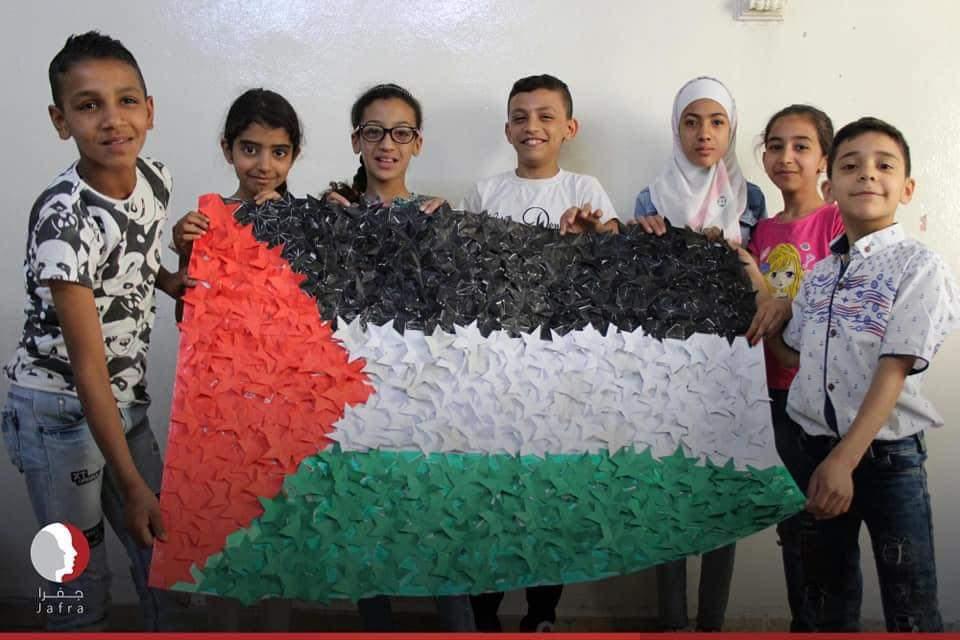"""أطفال في مركز """"جرمانا"""" في دمشق مبتسمون بانجاز العلم الفلسطيني الذي صنعوه بأنفسهم"""