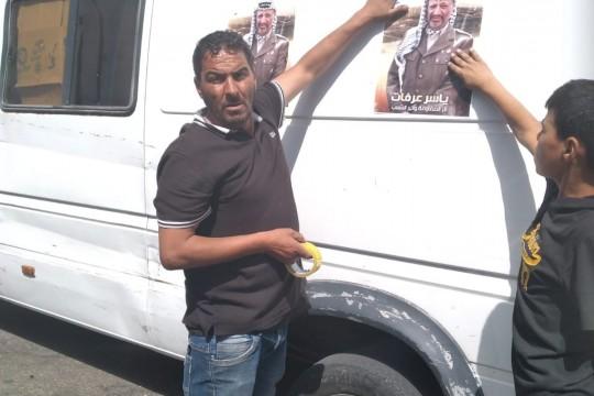 مواطن يقوم بالصاق صور الشهيد ياسر عرفات على المركبات في الخليل استنكارا لمحاولة الإساءة اليه